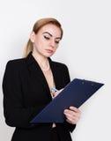 写的有吸引力的精力充沛的女商人压料板和采取笔记 免版税库存图片