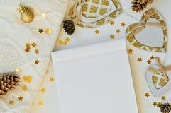 写的舒适不可思议的圣诞节背景在笔记本一个空白纸在白色的与锥体、毛线衣、星和装饰 顶视图 库存图片