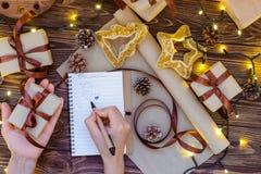 写礼品单的顶视图女性手在笔记本为被爱的人为圣诞节在与装饰, garlan的光的木桌 库存照片