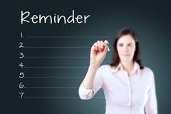 写空白的提示名单蓝色背景的女商人 免版税库存图片