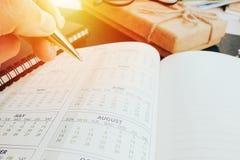 写空白的计划笔记本的手在书桌使用我们组织者日程表生活或企业计划者概念 免版税图库摄影