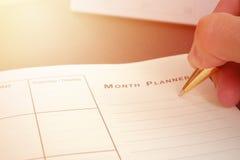 写空白的计划笔记本的手在书桌使用我们组织者日程表生活或企业计划者概念 免版税库存图片