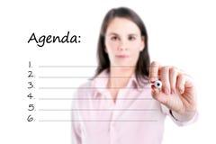 写空白的议程名单的年轻女商人。 库存图片