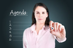 写空白的议程名单的年轻女商人。 免版税库存图片
