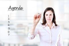 写空白的议程名单的年轻女商人。 免版税库存照片