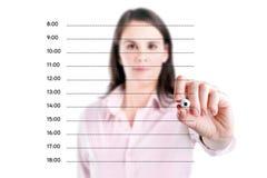 写空白的任命日程表的年轻女商人。 免版税库存照片