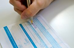 写笔的商人在存款单 免版税库存照片
