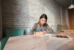 写笔的迷人的亚裔妇女在合同 免版税库存照片