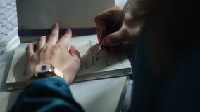 写笔记的女孩的特写镜头在一张白色桌上说谎在一个白色键盘附近的她的笔记本 股票录像