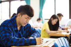 写笔记的小组年轻学生在教室 免版税库存照片