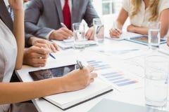 写笔记的董事的中间部分在证券交易经纪人行情室会议 库存照片