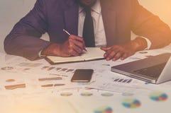 写笔记的选择聚焦年轻商人在与聪明的电话和膝上型计算机估计的商业文件 免版税库存照片