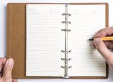 写给空的日志笔记本的手 免版税库存图片