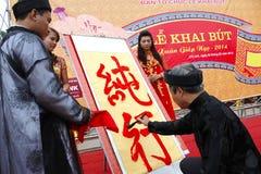 写艺术信的书法家为访客在寺庙 库存图片