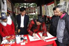 写艺术信的书法家为访客在寺庙 免版税库存图片