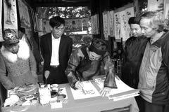 写艺术信的书法家为访客 免版税库存照片
