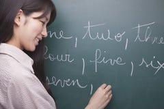 写英国数字的微笑的少妇学生在黑板 库存图片