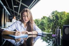 写计划集中的镜片的年轻女人学生在笔记薄,当传送信息在机动性时 沉思行家女孩i 免版税库存照片