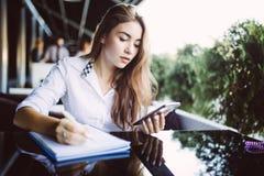 写计划集中的镜片的年轻女人学生在笔记薄,当传送信息在机动性时 沉思行家女孩i 库存图片