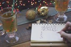 写2018个目标在笔记本,两个茶杯,圣诞节树的手戏弄 免版税库存图片