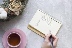 写2018个目标的手在笔记本,午后茶会杯子,圣诞节花圈 库存图片