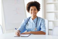 写给剪贴板的愉快的女性医生或护士 免版税图库摄影