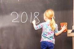 写2018年的逗人喜爱的小女孩在黑板 库存照片