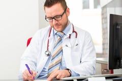 写医疗处方的年轻医生 库存照片