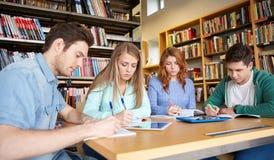 写给笔记本的愉快的学生在图书馆 免版税库存照片