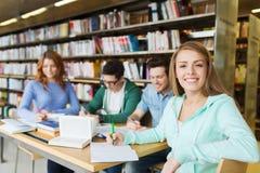 写给笔记本的愉快的学生女孩在图书馆 免版税库存图片