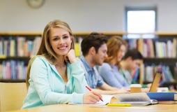 写给笔记本的愉快的学生女孩在图书馆 免版税图库摄影