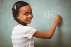 写ABC的逗人喜爱的小女孩在黑板 免版税图库摄影