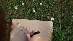 写ECO的女性手在放置绿色春天草的纸 股票录像