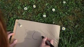 写ECO的女性手在放置绿色春天草的纸 股票视频