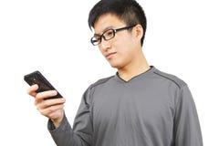 写SMS的人在移动电话 库存图片
