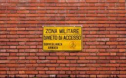 军事区域,没有通入 武装的监视 警报信号意大利语在砖墙背景 免版税库存照片