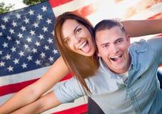 军事在美国国旗前面的夫妇贪心骑马 库存照片