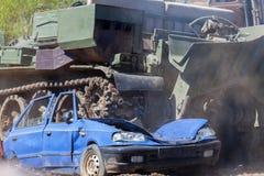 军事坦克击碎一辆蓝色汽车 库存照片