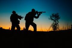 军事战士剪影有武器的在晚上 射击, hol 免版税图库摄影