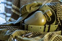 军事烧瓶、盖帽和阿丽斯围绕说谎在与a的橄榄色的shemagh 免版税库存照片
