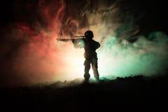 军事狙击手剪影有狙击手枪的在黑暗的被定调子的有雾的背景 射击,拿着枪,五颜六色的天空,背景 免版税库存照片