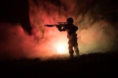 军事狙击手剪影有狙击手枪的在黑暗的被定调子的有雾的背景 射击,拿着枪,五颜六色的天空,背景 库存照片