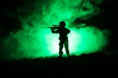 军事狙击手剪影有狙击手枪的在黑暗的被定调子的有雾的背景 射击,拿着枪,五颜六色的天空,背景 库存图片