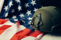 军事盔甲和美国国旗在背景 库存图片