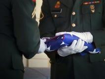 军事仪仗队折叠美国旗子在经验丰富的葬礼 免版税图库摄影