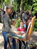军便帽的图画女孩有画架的在公园 免版税库存图片
