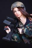 军服的妇女有在shoul的一杆攻击步枪的 图库摄影