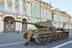 军服的战士在一个中型油箱T-34-85附近站立在 免版税库存照片