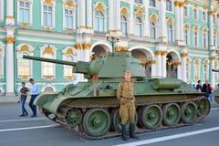 军服的战士在Th的一个中型油箱T-34附近站立 图库摄影