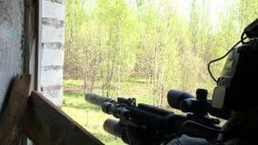军服的狙击手有在位置的武器的在一个被毁坏的房子 股票录像